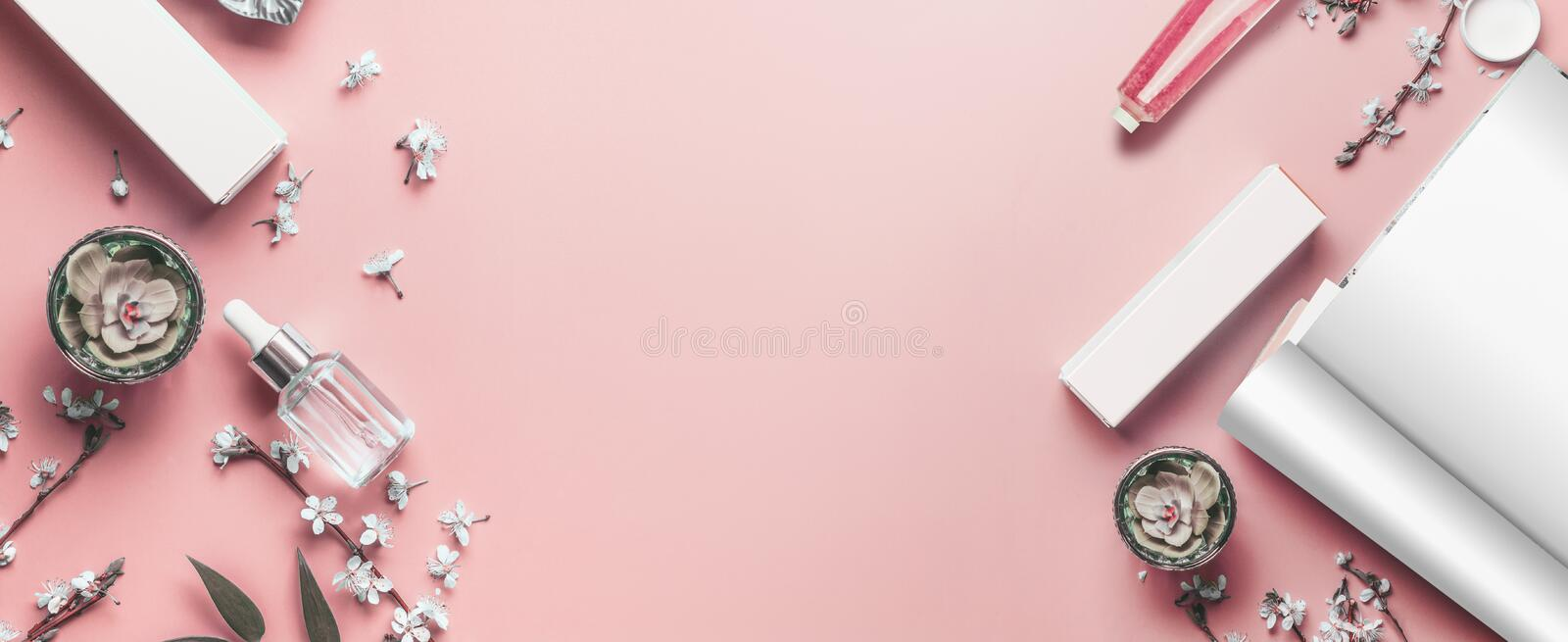 Pastel pink beauty desktop background with open magazine mock up, modern cosmetics and blossom branches, top view. Fashion blog royalty free stock image