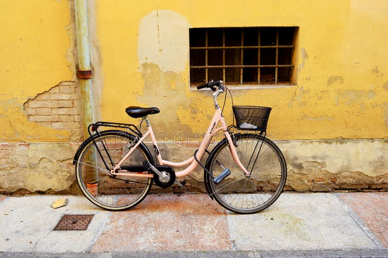 Pink bike parked in Modena. Pastel pink bike with pink and white pavement and vivid yellow background. Parked bike. Aesthetically pleasing colours in Modena royalty free stock photo