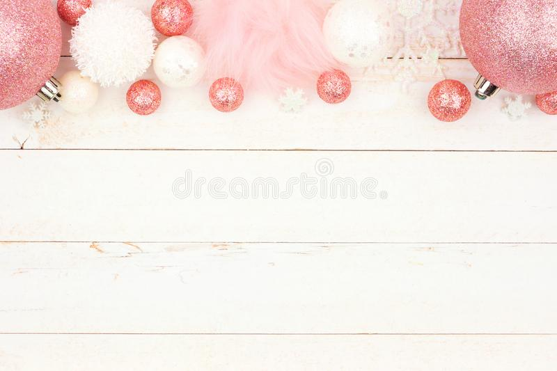 Pastel pink Christmas decoration top border over white wood royalty free stock photo
