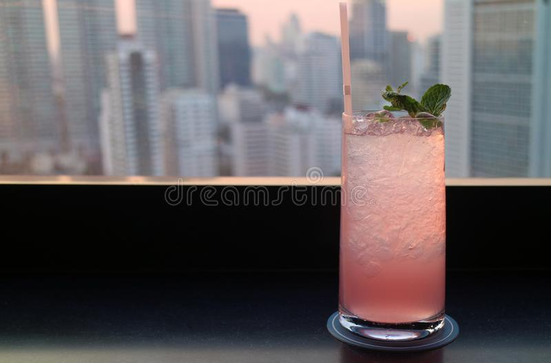 Pastel pink cocktails against blurry skyscrapers view at sunset. Relaxing time aerial alcohol architecture bar beverage black building chill chilled city stock image