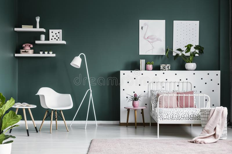 Pastel pink decorations in a scandi bedroom interior for a teenage girl with modern, white furniture and dark green walls stock photos