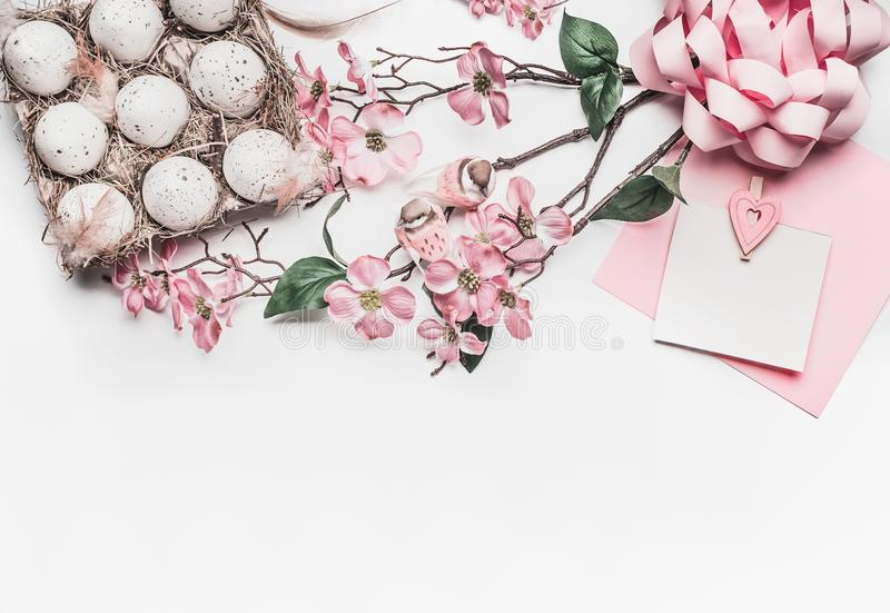 Pastel pink Easter greeting card mock up with blossom decoration, feathers, eggs in carton box on white desk background, top view royalty free stock photo