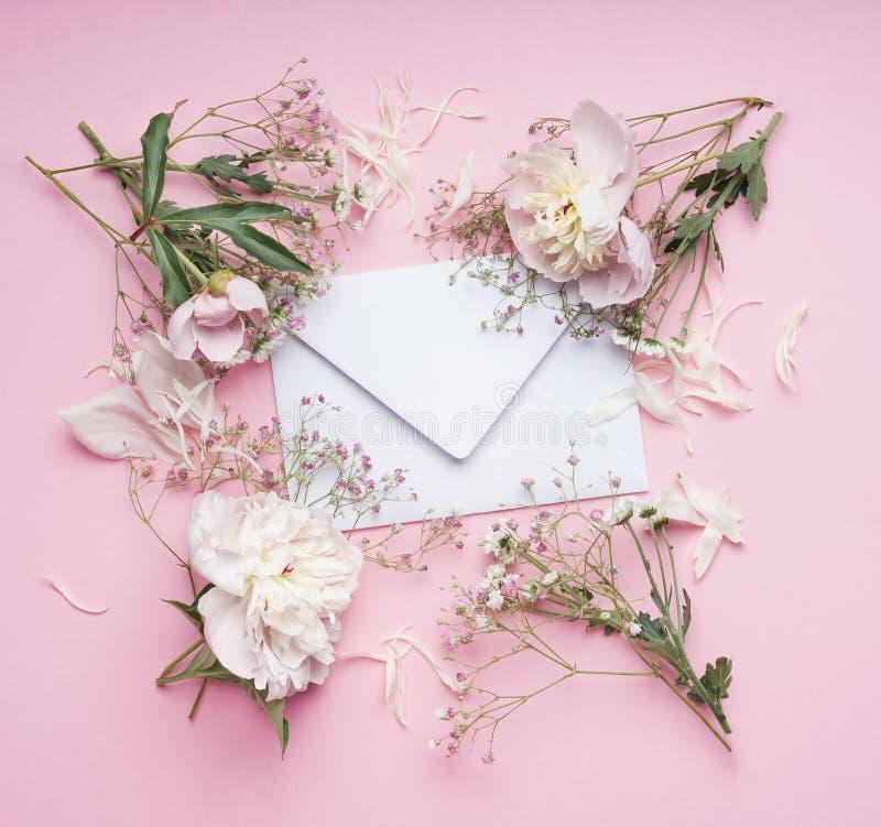 Pastel pink flowers around White envelop , floral arrangement. Top view royalty free stock photo