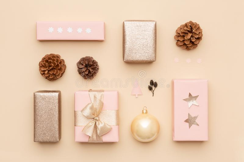 Pastel pink and gold minimal christmas background. Beautiful nordic christmas gifts isolated on beige background. Pink gift boxes. stock images