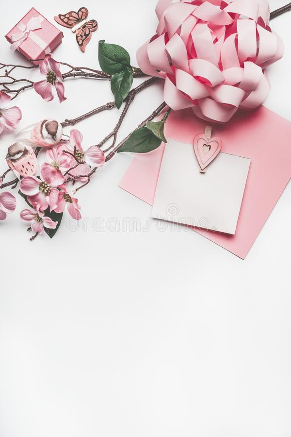Pastel pink greeting card mock up with blossom decoration, hearts, little gift box and bow stock images