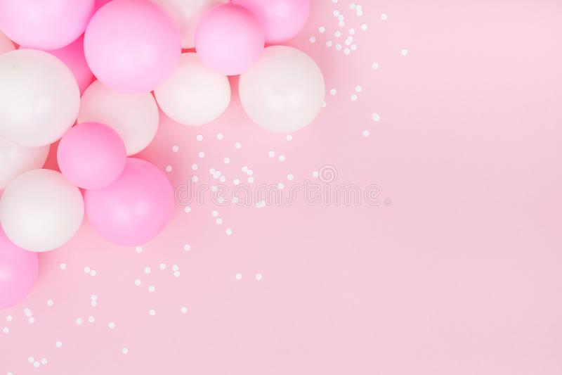 Pastel pink table with colorful balloons and confetti for birthday top view. Flat lay style. stock photo