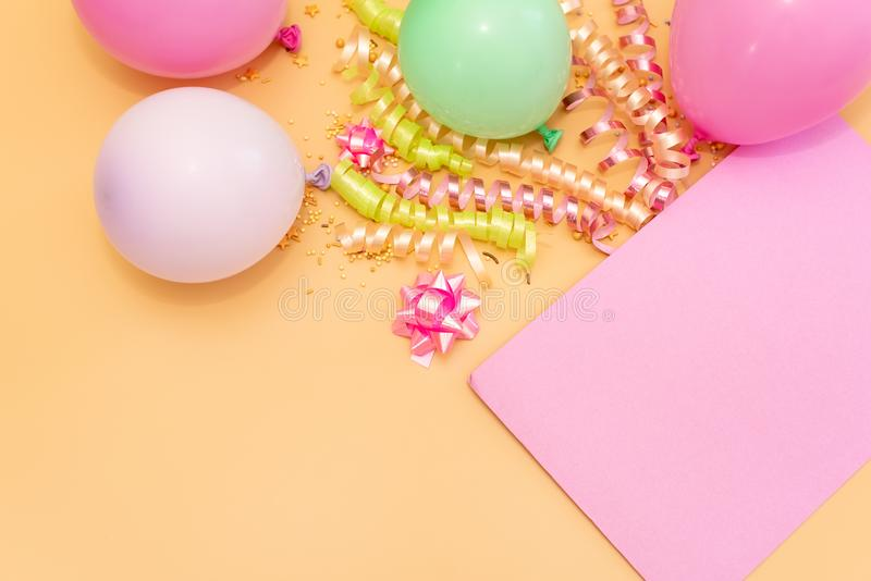 Pastel pink table with frame from balloons and confetti for birthday top view. Flat lay composition stock images