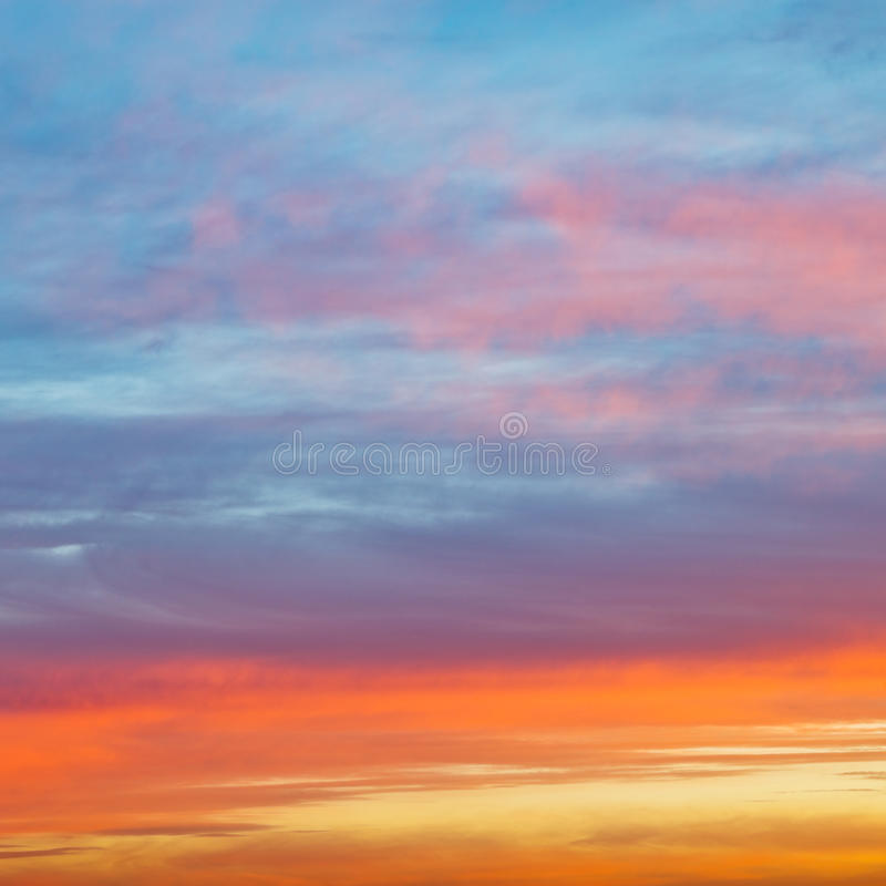 Pastel pink and yellow sunrise clouds in blue sky stock images