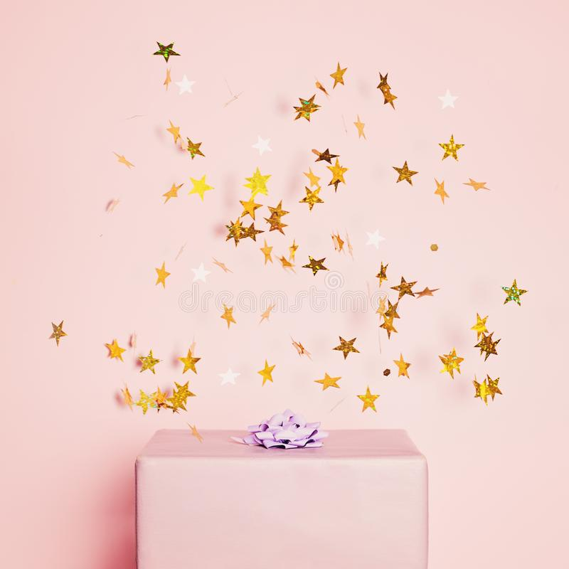 Pastel purple gift box with gold confetti stars on pink background. Holiday concept for Birthday card, Christmas, Mothers day royalty free stock images