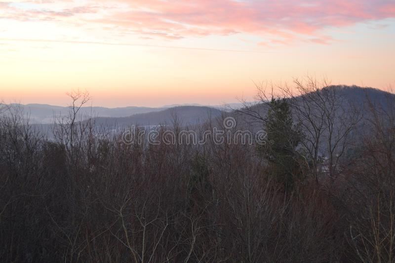 The pastel sunset. Viewed through the trees over the mountain landscape stock images