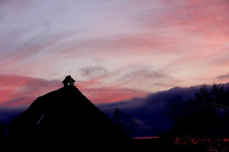Pastel Sunset on the roof. Pastel toned sunset with roof siluet are wonderful to see and even more wonderful to take photos of this magical moment royalty free stock photography