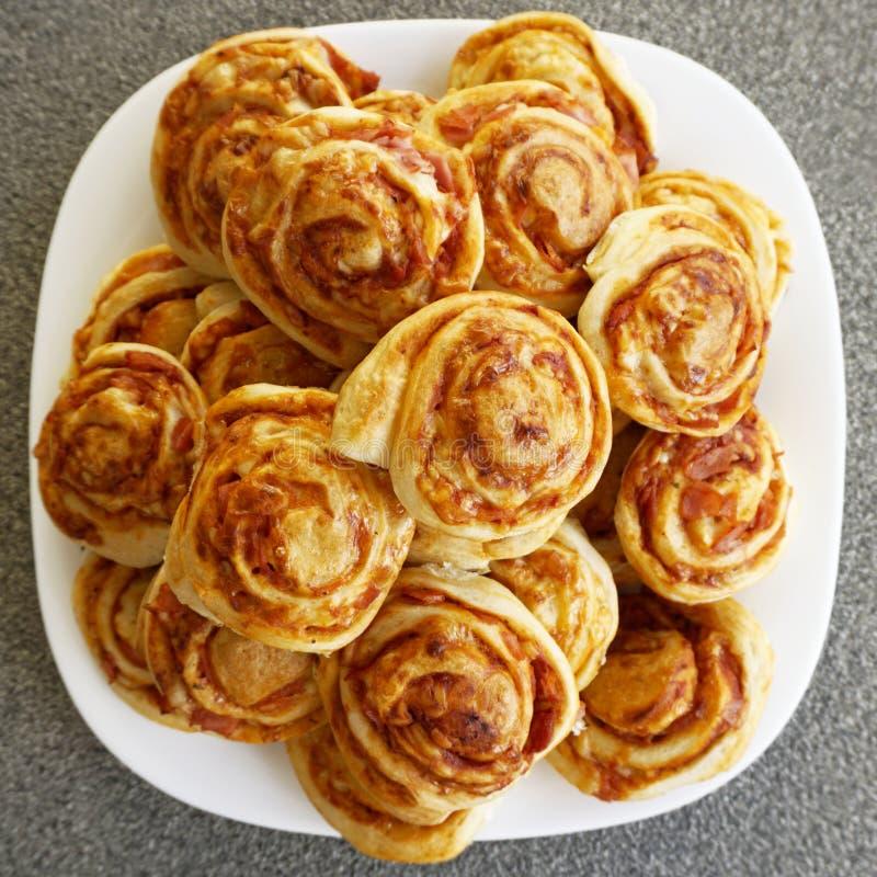A pastelaria caseiro cozida rola no gosto da pizza, com presunto e queijo imagem de stock