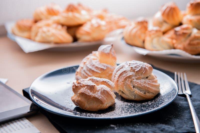 Pastelaria de três crostas enchida com o creme com açúcar pulverizado na placa azul fotografia de stock