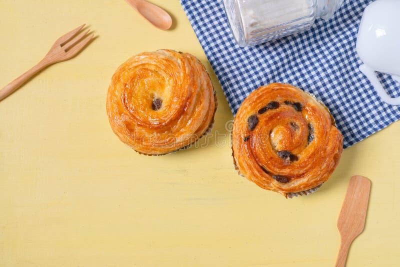 A pastelaria dinamarquesa da passa na madeira amarela e o guingão azul verificam c foto de stock royalty free