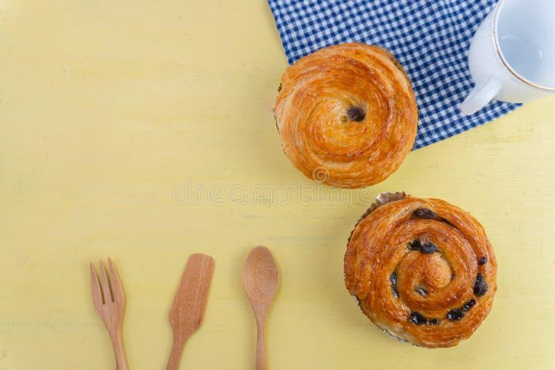 A pastelaria dinamarquesa da passa na madeira amarela e o guingão azul verificam c foto de stock