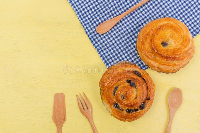 A pastelaria dinamarquesa da passa na madeira amarela e o guingão azul verificam c imagens de stock royalty free