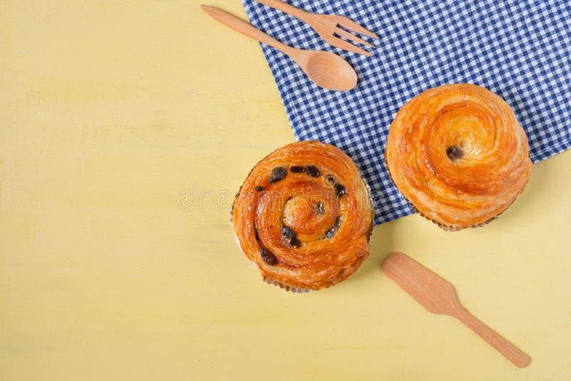 A pastelaria dinamarquesa da passa na madeira amarela e o guingão azul verificam c imagens de stock