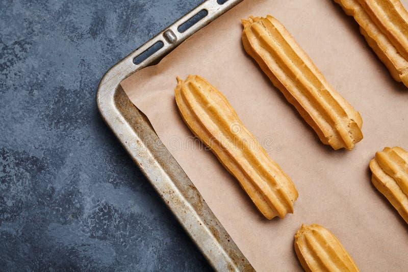 Pastelaria francesa tradicional dos Eclairs na folha de cozimento com quadro vazio fotos de stock