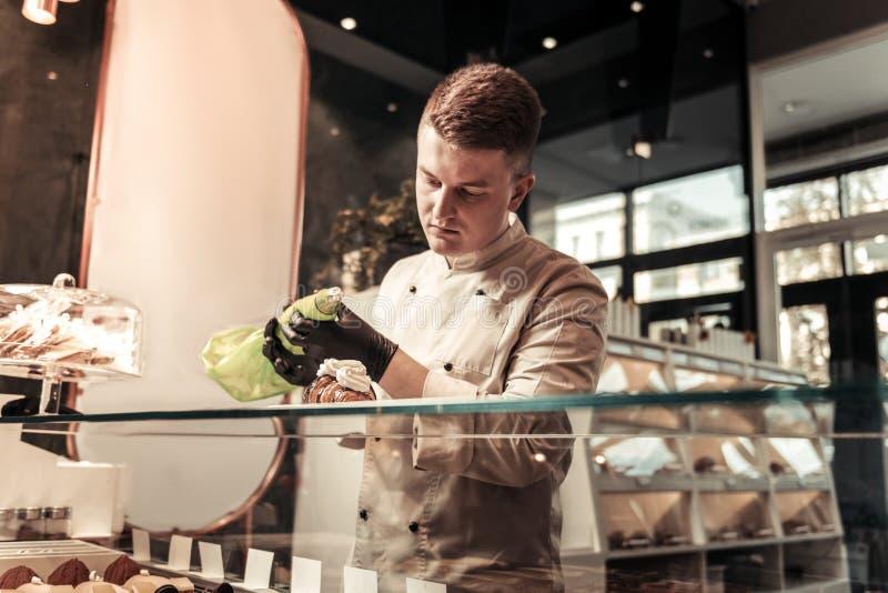 Pasteleiro esperto sério que guarda um saco da pastelaria fotografia de stock royalty free
