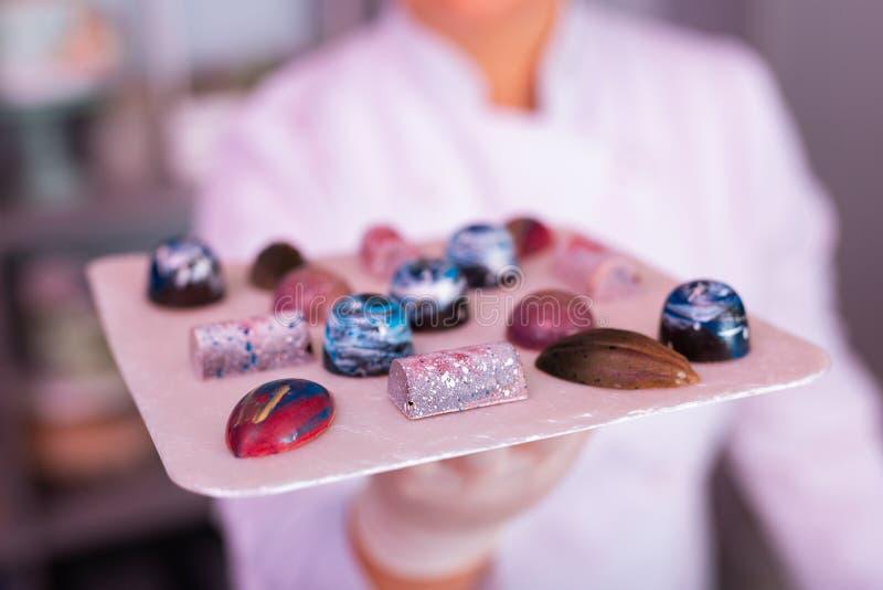 Pasteleiro experiente que olha a placa com chocolates criativos foto de stock