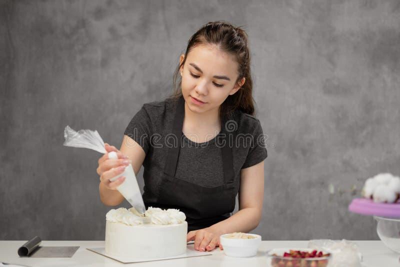 Pasteleiro no trabalho Bolo de creme que decora Cozinhe a tabela que prepara um bolo imagem de stock royalty free