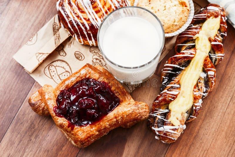 Pasteles, bollos, torta de las natillas, un vidrio de leche en la tabla Primer imágenes de archivo libres de regalías