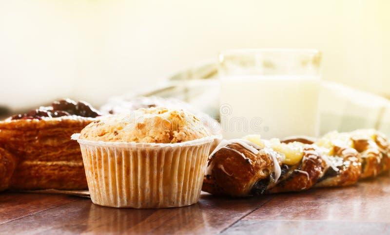 Pasteles, bollos, torta de las natillas, un vidrio de leche en la tabla Primer imagen de archivo libre de regalías