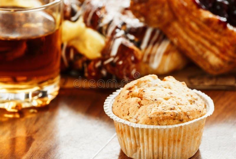 Pasteles, bollos, torta de las natillas, un vidrio de zumo de manzana en la tabla Primer foto de archivo libre de regalías