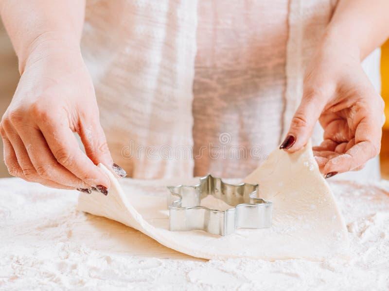 Pasteles caseros del cortador de la galleta de las manos de la mujer que cuecen imagen de archivo