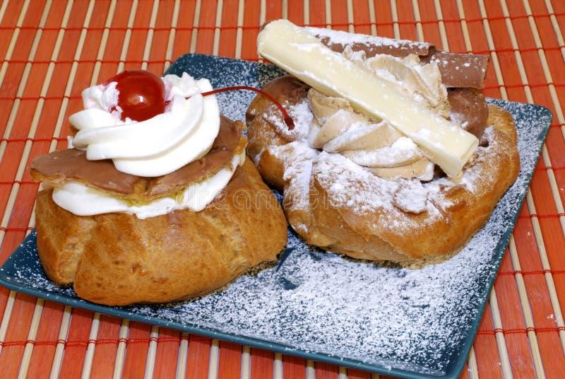 Pasteles con la fruta y la crema azotada. fotos de archivo