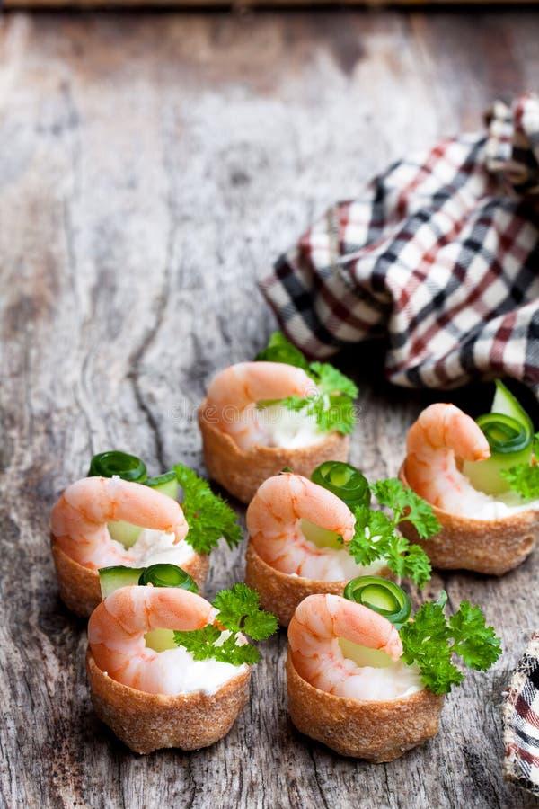 Pasteles curruscantes salados de los croustades rellenos con el queso cremoso y las gambas en la tabla de madera foto de archivo