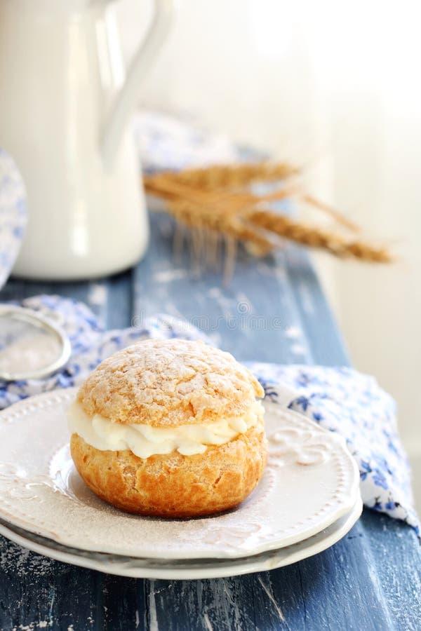 Pasteles de los Choux rellenos con crema en dos platillos blancos imagen de archivo