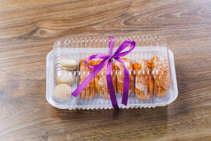 Pasteles de los Eclairs en caja de la ampolla imagenes de archivo