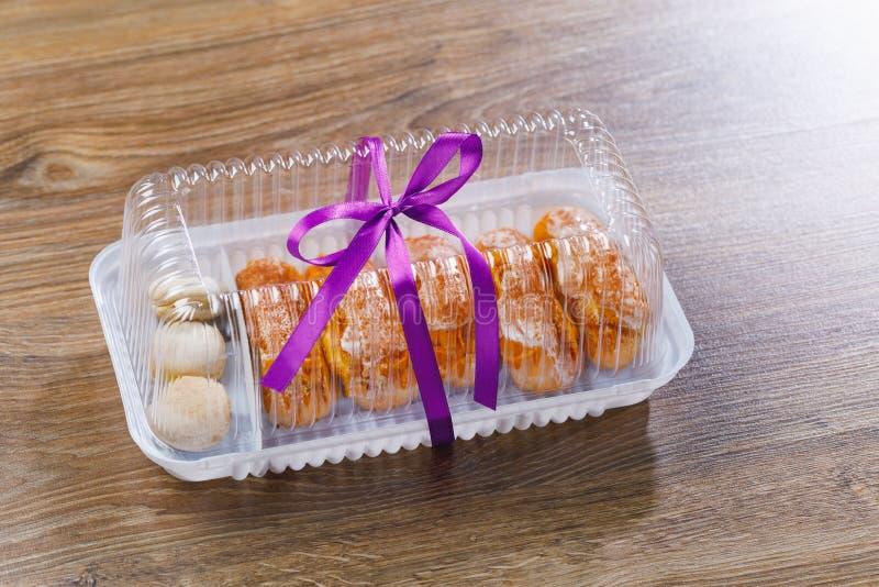 Pasteles de los Eclairs en caja de la ampolla foto de archivo