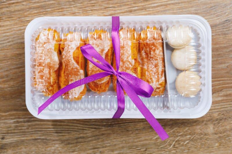 Pasteles de los Eclairs en caja de la ampolla fotografía de archivo
