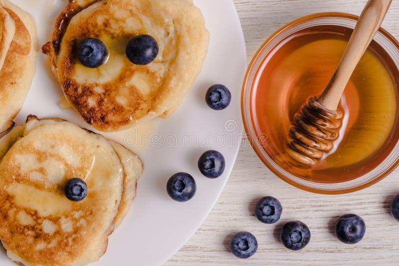 Pasteles de queso en una placa con los arándanos, la placa derecha con la miel y una cuchara de madera para la miel foto de archivo