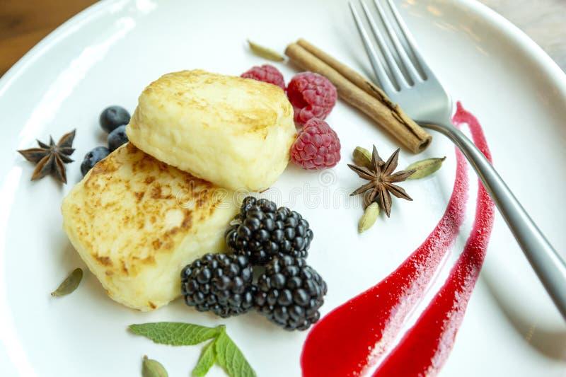 Pasteles de queso de la cuajada en una placa con las bayas Primer delicioso y sano del desayuno Platos del hermoso diseño foto de archivo libre de regalías