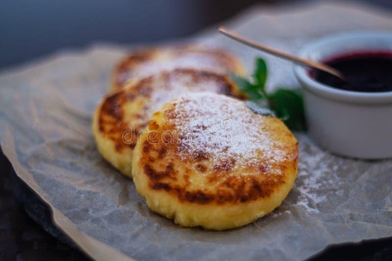Pasteles de queso o crepes fritos en el documento del arte sobre la placa de piedra con el atasco del arándano imagenes de archivo