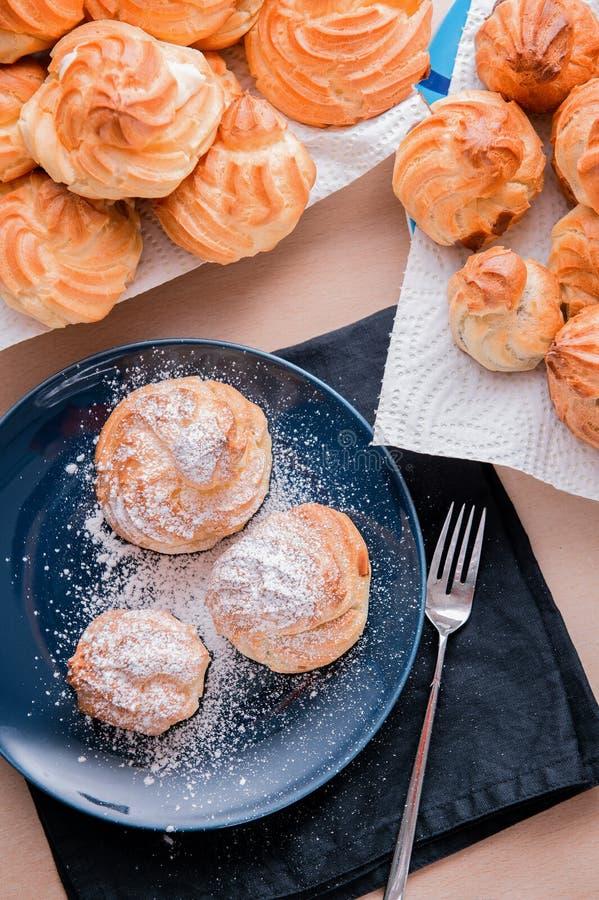 Pasteles de tres cortezas llenados de crema con el azúcar en polvo en la placa azul imágenes de archivo libres de regalías