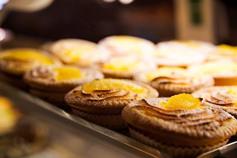 Pasteles dulces con el atasco en la ventana de la tienda fotos de archivo