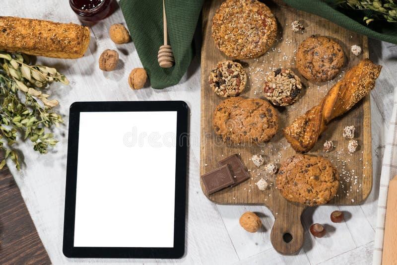 Pasteles dulces hechos en casa frescos con la tableta fotografía de archivo