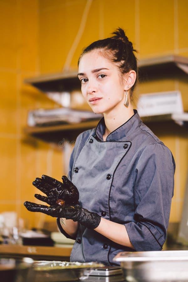 Pasteles sujetos de la profesión y el cocinar mujer caucásica joven con el tatuaje del chef de repostería en la cocina del restau fotografía de archivo libre de regalías