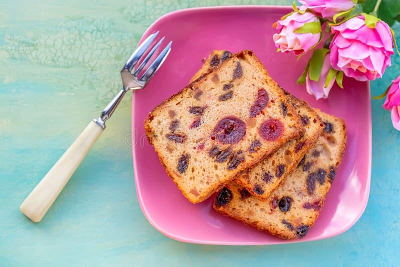 pasteles Una rebanada de la torta con las frutas en una placa rosada Pasa y cereza de la torta de la fruta imagen de archivo libre de regalías