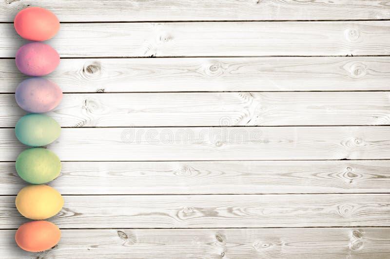 Pastelkleur gekleurde eieren op witte houten planken, Pasen-achtergrond stock fotografie