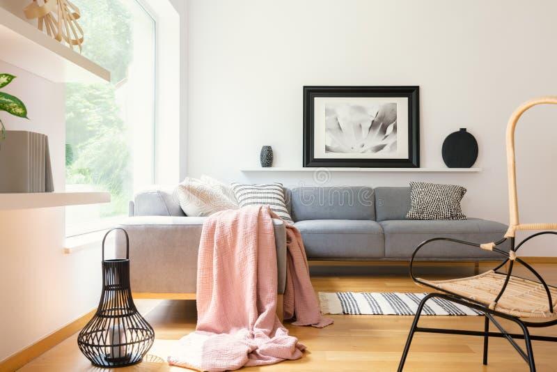 Pastelkleur roze die deken op hoeklaag wordt geworpen die zich in wit woonkamerbinnenland bevinden met eenvoudige affiche, lantaa royalty-vrije stock afbeeldingen