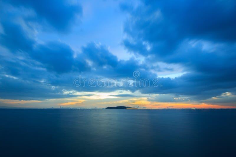 Pastelkleurzonsondergang over de oceaan in een bewolkte hemel royalty-vrije stock foto
