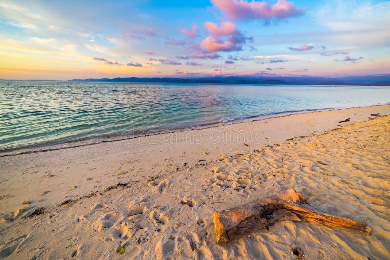 Pastell färbte Himmel, Wolken und Meerblick an der Dämmerung Weitwinkelansicht vom sandigen Strand mit Stammfragment im Vordergru lizenzfreies stockfoto