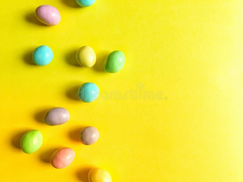Pastell-Ostern-Süßigkeit auf hellem gelbem Hintergrund stockfotos