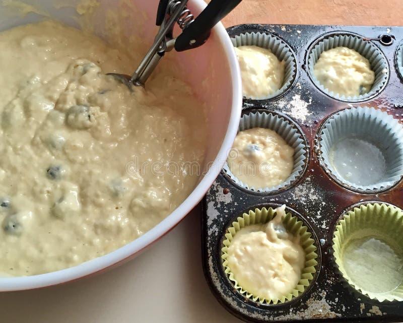 Pastella di scavatura del muffin ai mirtilli nelle tazze per cuocere immagine stock libera da diritti