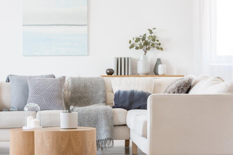 Pastellblå och vit, abstrakt oljemålning på tom vit vägg med konsolbord med blommor i vase och böcker fotografering för bildbyråer